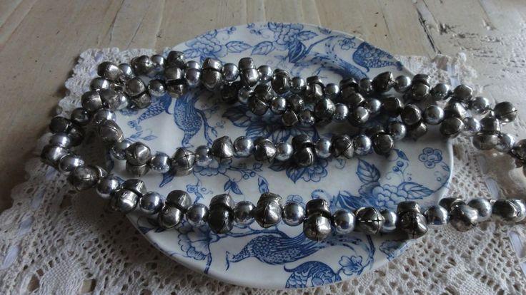 KERST slinger met belletjes     Telkens 2 belletjes en dan een kunststof zilveren bolletjes.Bolletjes: doorsnede 1,1 cm.Totale lengte 111cm.Met normale gebruikssporen.