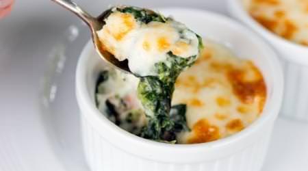 Eier mit Spinat  Zutaten für eine Portion: 250 g Spinat (roh) 1/2 Zwiebel 1 EL Olivenöl 15 g Parmesankäse (gehobelt) nach Belieben Salz & Pfeffer 1 Prise Muskatnuss (gemahlen) 1 EL Saure Sahne 2 Eier 75 g Käse (gerieben, fettarm)