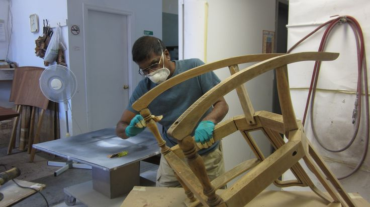 Sanding the racking chair by AM Furniture Finishing.