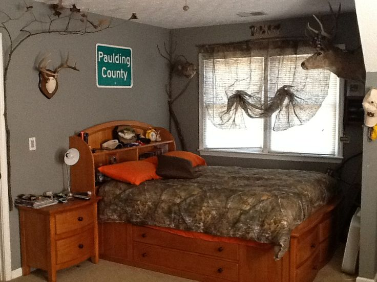 My sons redneck hunting bedroom with camo curtains, treetrunk curtain rod, camo bedspread and tree limbs attached around the room.