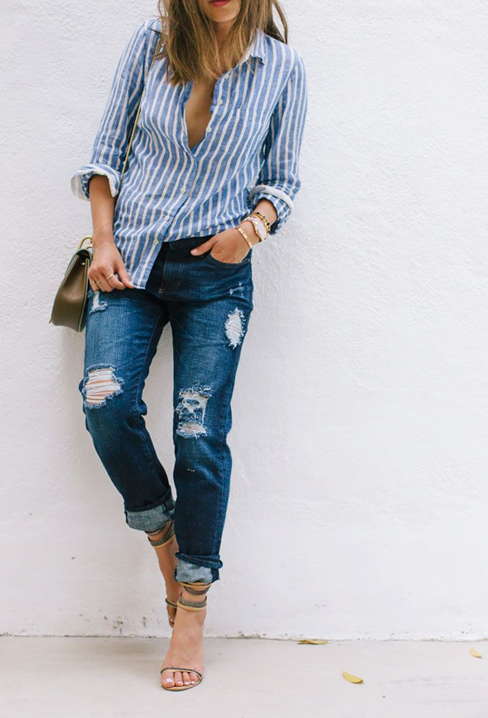 Aimee Song of Song of Style wears a striped button-down top, distressed boyfriend jeans, strappy neutral sandals and mixed metals