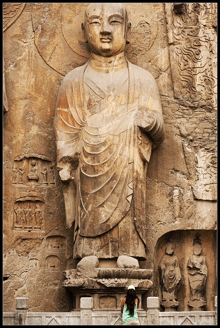 Lone Admirer - Buddhist carvings at the UNESCO World Heritage site in Luoyang. - Luoyang, Henan, China - Daily Travel Photos - Once Daily Images From Around The World - Travel Photography - Travel Stock Photos