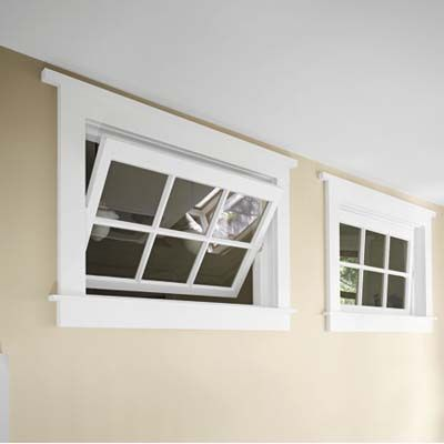 Two 1920s schoolhouse transom windows the homeowner found at a salvage yard let natural light from the big stairwell window reach the children's bathroom