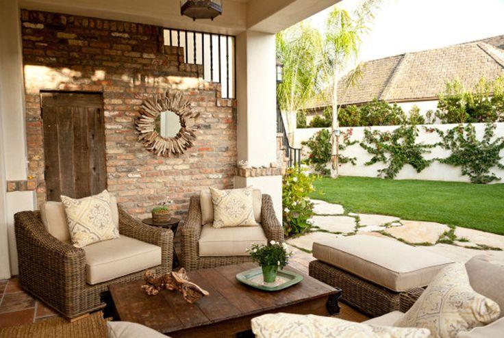 Плетеная мебель и открытая кирпичная кладка смотрятся вполне уместно на террасе средиземноморского стиля.