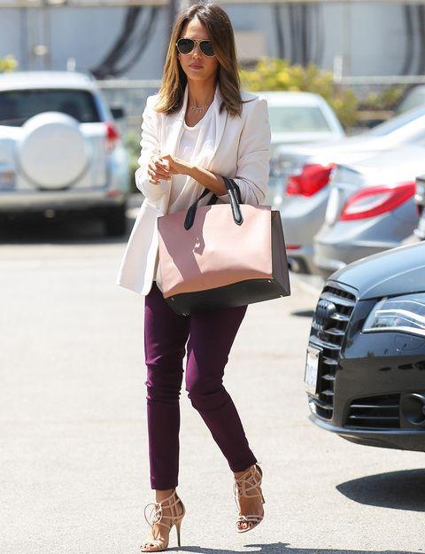 Jessica Albafirma un perfecto look de día para ir a la oficina con este estilismo a base de blazer y blusa en blanco, pantalones morados, sandalias nude y bolso bicolor en rosa palo y negro.