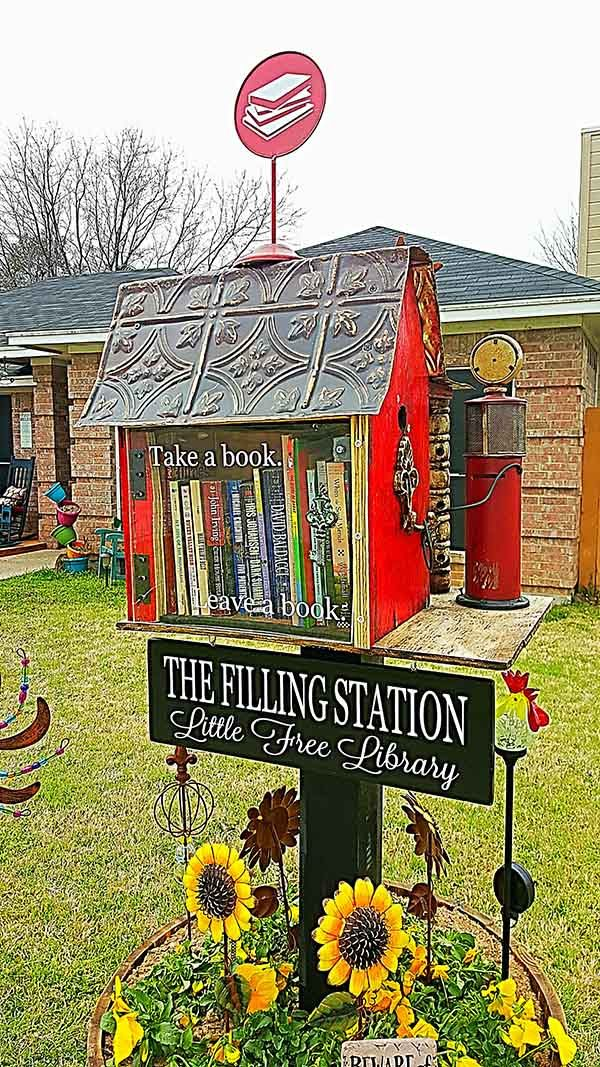 """Kim Johnson. Watauga, TX. My husband is a car fanatic. I am a bibliophile. We had been talking about a Little Free Library for awhile and then he decided it was going to be my Valentine's Day gift. He found a beautiful birdhouse and fixed it up so it is pretty from both sides. It's a """"Filling Station"""" library and even has a tiny gas pump. We hope you will come exchange a book or two and fill up your reading list for a while!"""