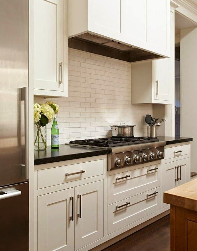 Traditional white kitchen with subway tile back splash and stainless steel appliances.