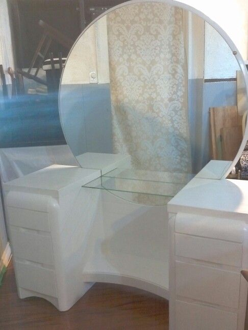 Vintage dressing table with round mirror and glass shelf.