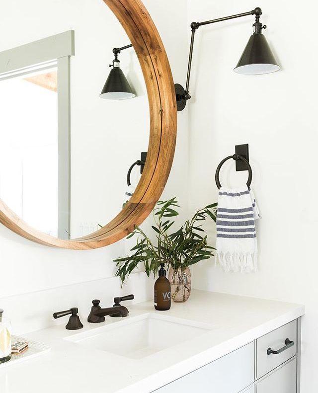 Wood framed round mirror farm sink with dark faucet, striped bathroom hand towel. Boho feel