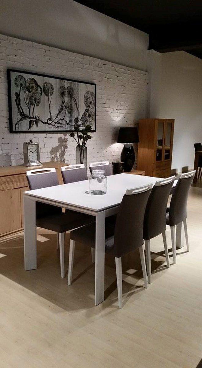 Minimalistyczny komplet jadalniany: biały, prostokątny stół na 6 osób, tapicerowane szare krzesła z białymi nogami i poręcznymi uchwytami stanowiącymi górną część oparcia.