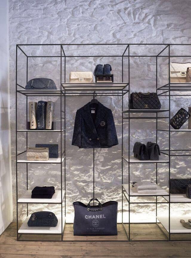 La forma simétrica de la estantería y el color , también la colocación de los productos y la iluminación de la pared hacen que esta tienda vaya totalmente acorde  con la imagen de marca