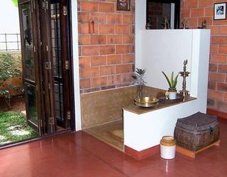 interesting spot with red-brick, nook, red oxide floor, dark wood door...