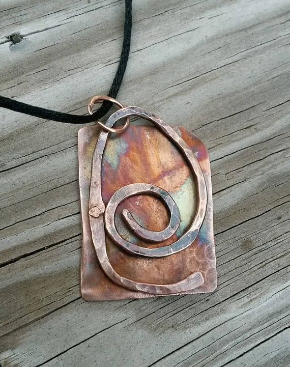 This rustic rectangular flame painted copper pendant necklace was upcycled from salvaged copper sheet and copper electrical wire. The sheet was flame painted to add some beautiful blue, yellow and pink hues to the copper backing. A piece of copper wire was formed, forged and heat treated before being riveted to the back plate. The one of a kind pendant hangs from a 21 black nylon cord by a handmade bail.