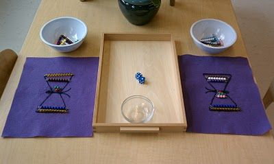 Montessori: the butterfly game played with colored bead stairs. Roll two dice to complete butterfly wings. Add sum of dice or use the two numbers separately to add beads. First person done wins.
