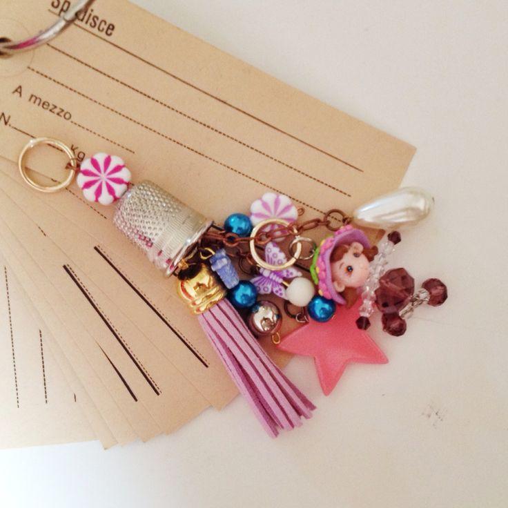 """Amuleto serie """"toys"""" realizzato con corallini in plastica, stella in plexy glass, bambolina in cristallo e nappa in suede crueltyfree"""