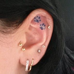 Two tiny paw prints. | 31 Ideas For A Delicate Inner-Ear Tattoo