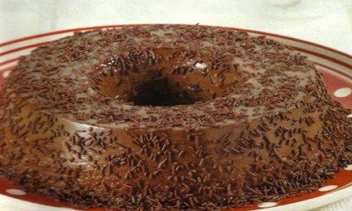 No liquidificador, bata o leite condensado, o chocolate, os ovos, a baunilha e o leite de coco até formar uma mistura homogênea.  Despeje em uma fôrma de buraco no meio untada, cubra com papel alumínio e leve ao forno, em banho-maria, por 40 minutos ou até