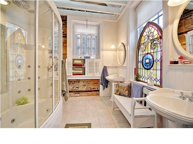 The stained glass window and the reclaimed brick help bring the outdoors indoors in this bathroom. #springintothedream