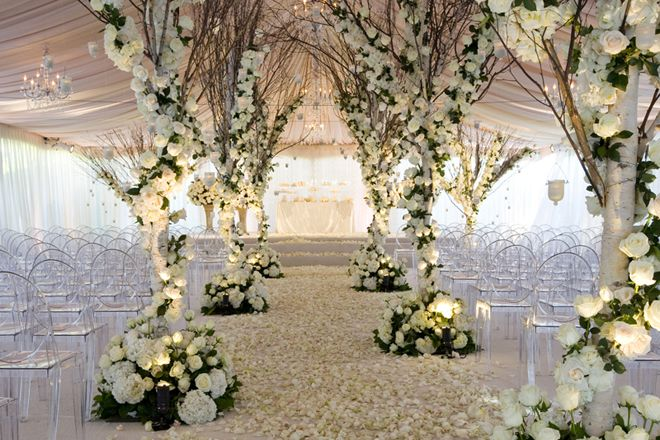 Tree branches weave with white roses. Petals decorate the floor. Clear plastic chairs. Marquee Wedding, winter feel. Ceremony Ideas for your big day, at Manor by the Lake www.manorbythelake.co.uk