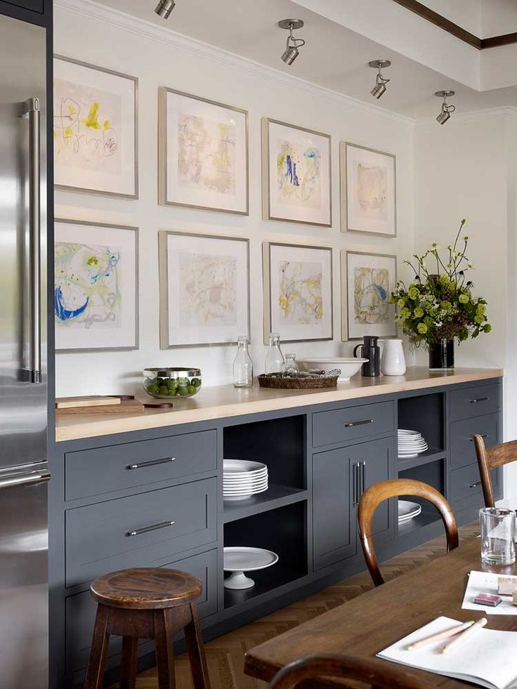 Shaker style dark grey kitchen/dining cabinetry. A softer look for kitchen storage in a more social area of the room. Love the mix of timbers on the table and the stool, as well as the clean lines of the worktop - echoed in the gallery effect above.
