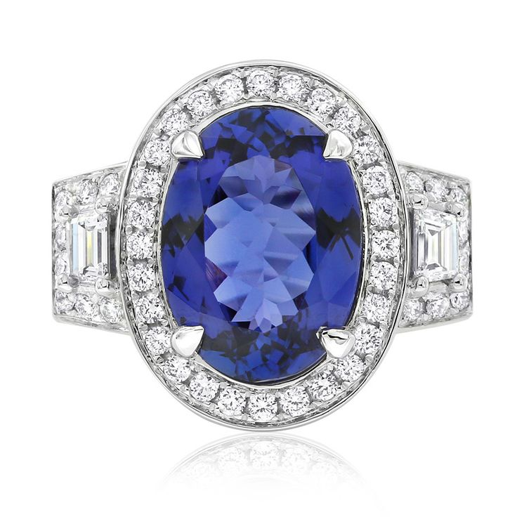 Rare and beautiful. Kilimanjaro tanzanite and diamond dress ring. This oval cut tanzanite is a deep bluish-purple colour and weighs 5.56ct. This ring features trapezoid and brilliant diamonds in a bold design. Crafted in 18ct white gold. This ring will be customised to perfectly fit your finger, which may take up to 6 weeks