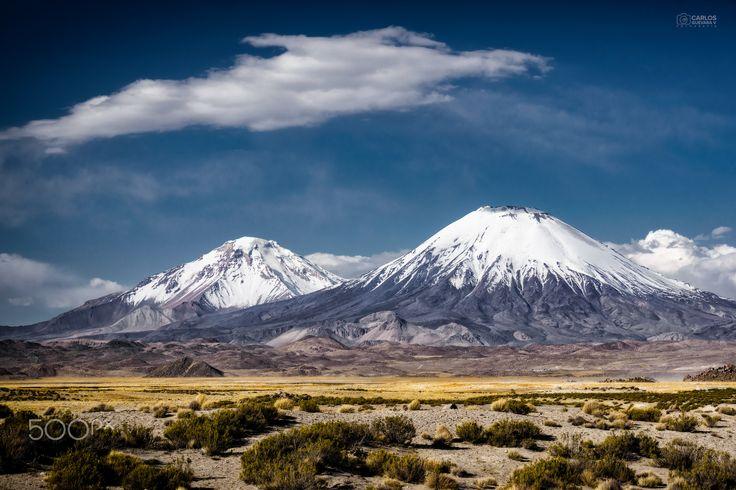 Nevados de Payachatas - Los Nevados de Payachatas son dos volcanes, el más cercano en esta imagen llamado Parinacota (6.348 msnm) y el Pomerape (6282 msnm). Se encuentran en el límite de Chile-Bolivia y asociados a ellos existe una bella leyenda incaica.