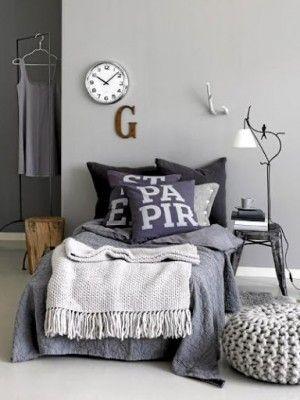 Slaapkamer in grijstinten en warme materialen.