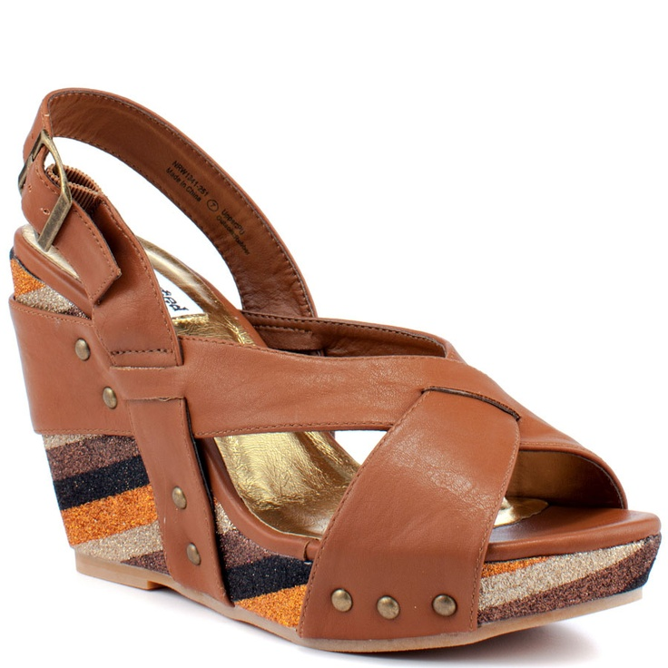A tan synthetic covers the crossing vamp and adjustable heel strap. A  striped and glittery 4 inch wedge and 1 inch platform ...