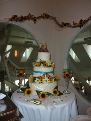 Handmade wedding cake with bunny cake topper and sunflowers, daisies and butterfly decorations. Made by the bride, maid of honor and groom's aunt.