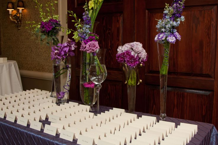 Eclectic flowers with varying purple hues on display on the escort card table at Harry's Savoy Ballroom.