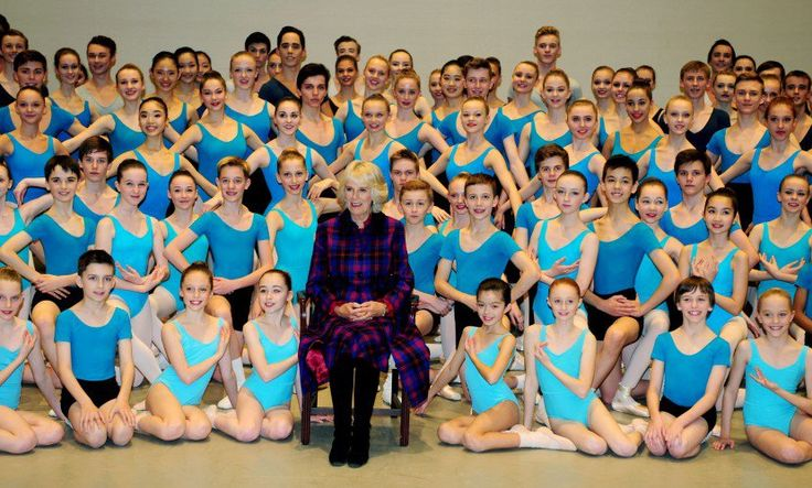 The Duchess of Cornwall, Camilla, sitting in the centre surrounded by the young ballerinas at Elmhurst School of Dance.