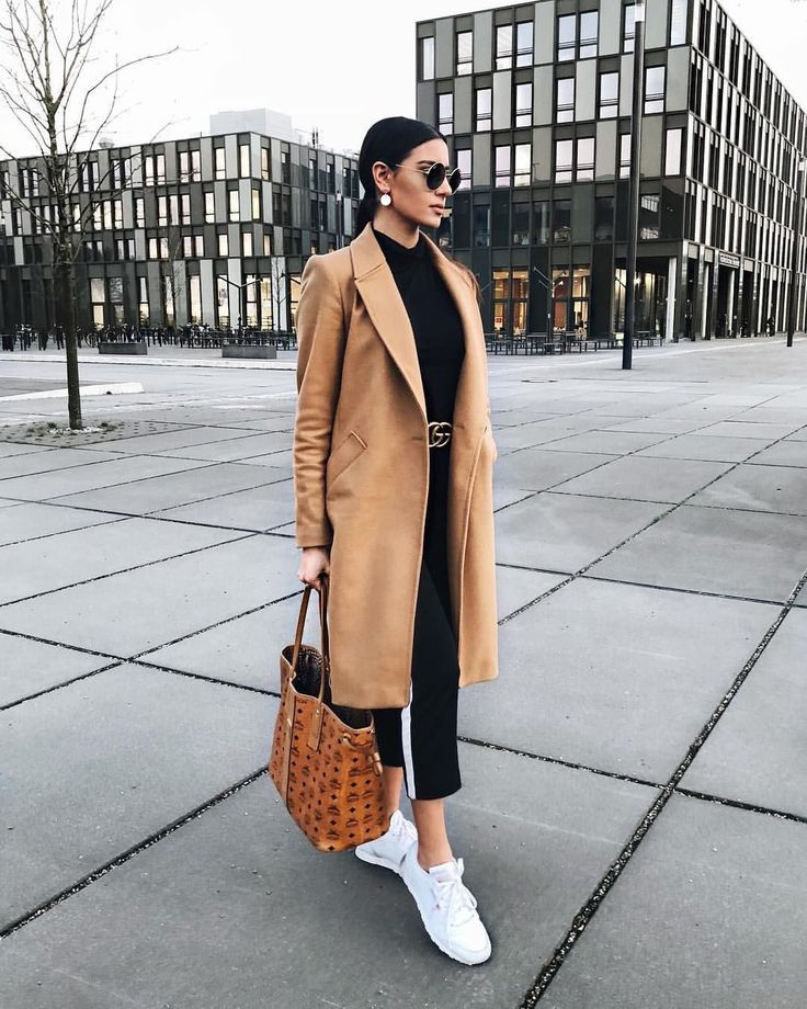 Classic camel coat over all black casual outfit with chic black leather belt.