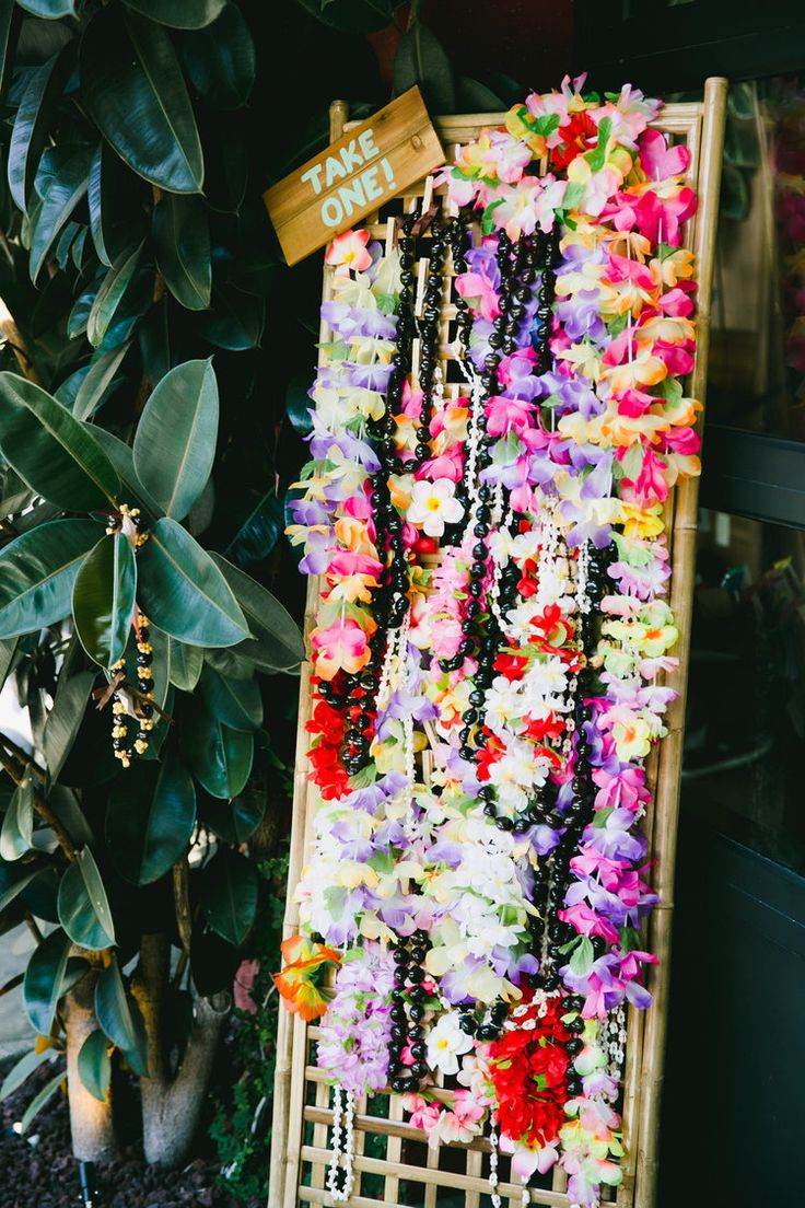 Modern Tiki Wedding Lei Display -- can get fake leis in bulk and everyone can get one on the way in to wedding....