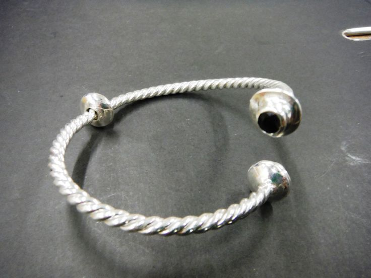Twisted wire cuff with stones set on the ends by Paul Bradley