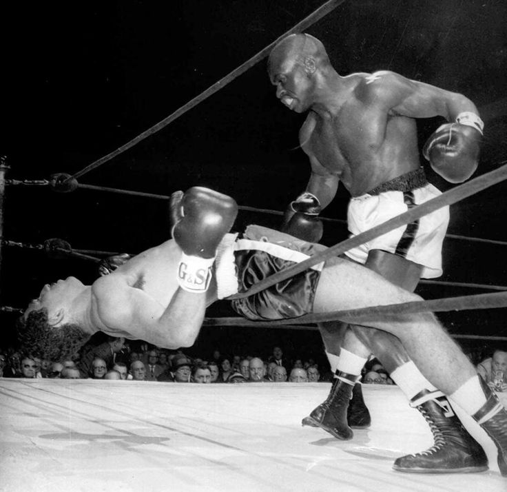 Rubin Hurricane Carter stands over Florentino Fernandez of Cuba fall through the ropes after Fernandez was knocked out in the first round of their fight.