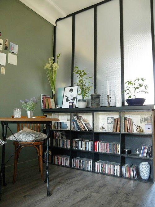 Une bibliothèque avec des caisses à vin devant une verrière.