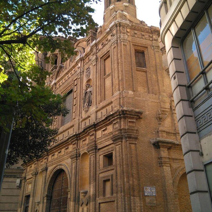 Laiglesia de la Manteríapertenecía al monasterio deSanto Tomás de Villanueva,mandado construir por el arzobispo de Zaragoza,Francisco Gamboa, y el obispo deHuelva,Bartolomé de Foncalda, entre 1663 y 1683. Desde 1883 forma parte de las escuelas de lasmadres escolapias.  En la actualidad, la fachada de la iglesia, flanqueada por dos torreoncillos, forma uno de los lados de la Plaza de San Roque, antiguamente llamada Plaza de la Mantería, en El Coso. El interior está completamente…