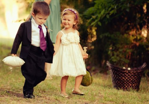 a precious flower girl and ring bearer taking a walk down the aisle
