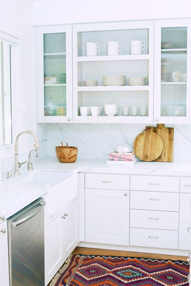 Bright white and gray marble backsplash, white drawers and cabinets with frosted glass fronts, deep basin sink, chrome appliances and rustic wood cutting boards. Love this mix of fresh, modern, organic, clean and minimalist styles in the kitchen. Such good inspiration for a kitchen remodel or makeover!