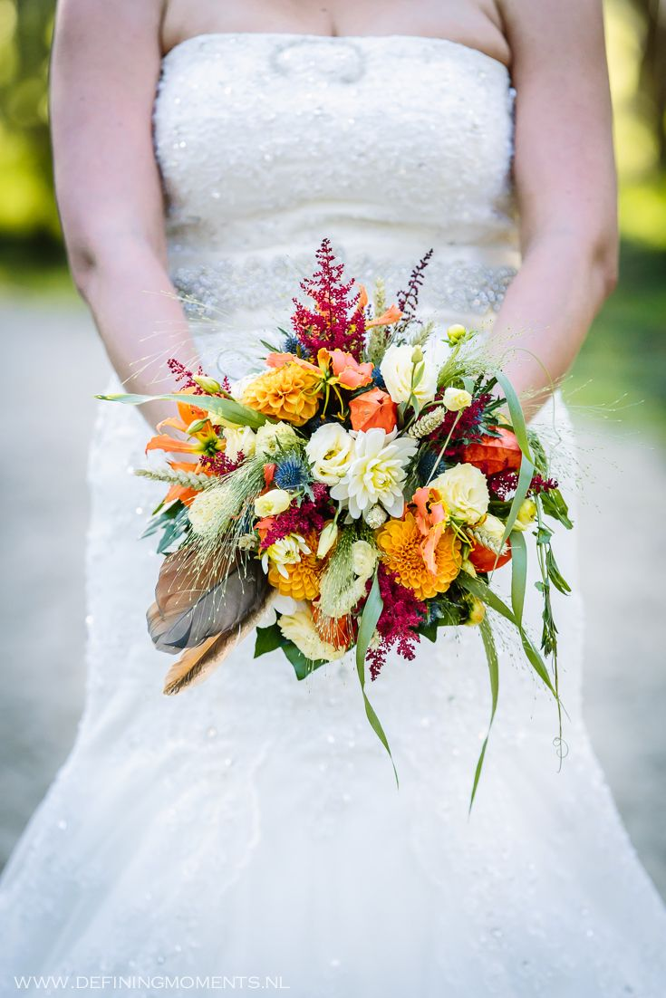Bruidsboeket in warme herfst-tinten met o.a. oranje dahlia's & kamperfoelie, witte rozen en veren. Wedding bouquet with warm autumn colours, composed of orange dahlia & honeysuckle, white roses and feathers.