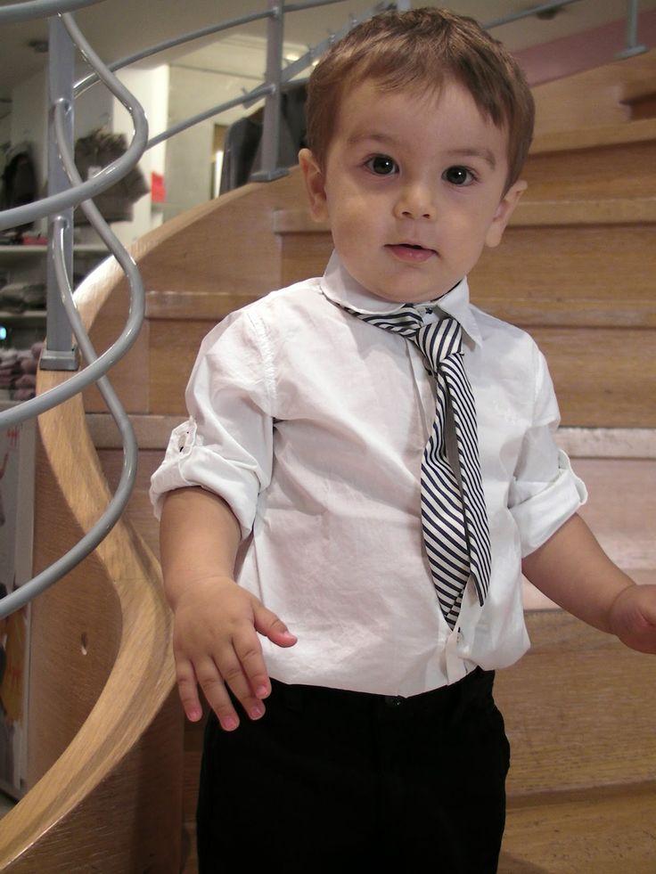 bimbo con pantaloni neri, camicia bianca e cravatta con righe bianche e nere