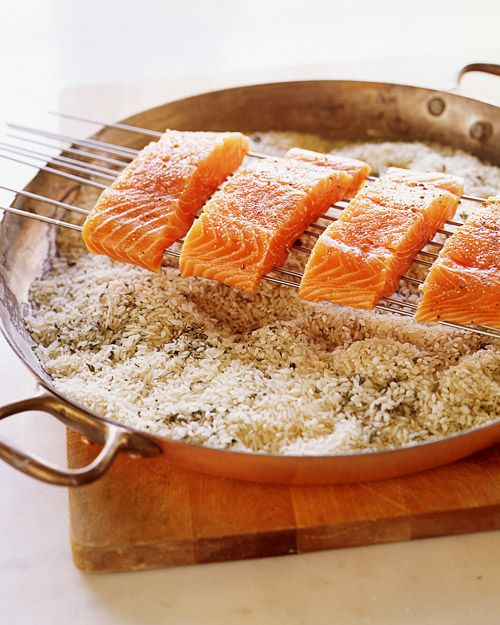Create a smoker by filling a shallow pan with a mix of white rice and herbs and laying metal skewers across the diameter.
