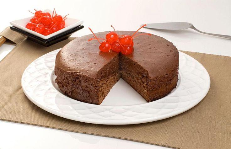 bolo-mousse de chocolate sobre o prato branco e decorado com cerejas