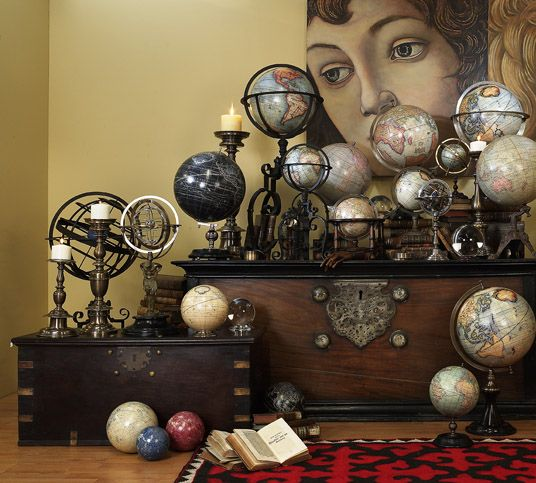 collection of globes displayed with vintage trunks