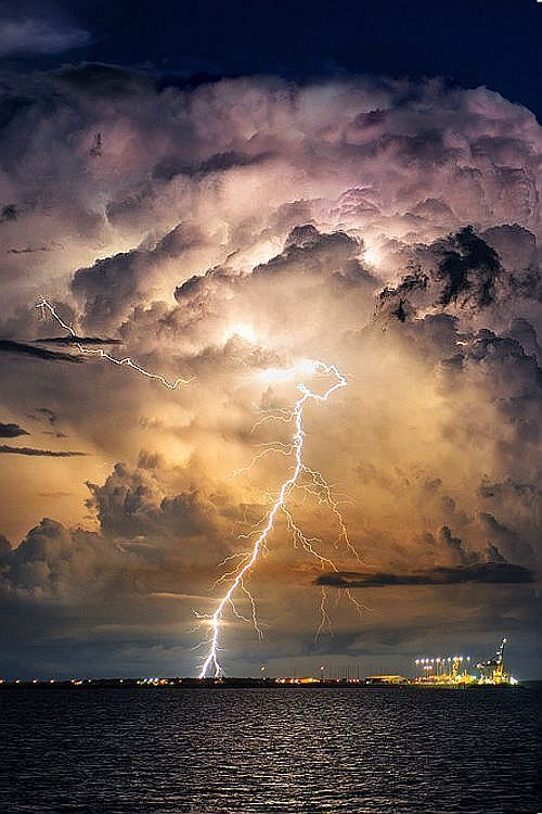 Dark sea and sky's clouds light up with a flash of a lightning bolt between the clouds and water. City lights in the distance.