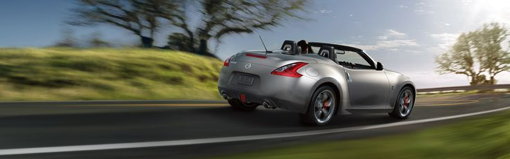 2016 Nissan 370Z Roadster shown in Gun Metallic, side view, driving through green landscape