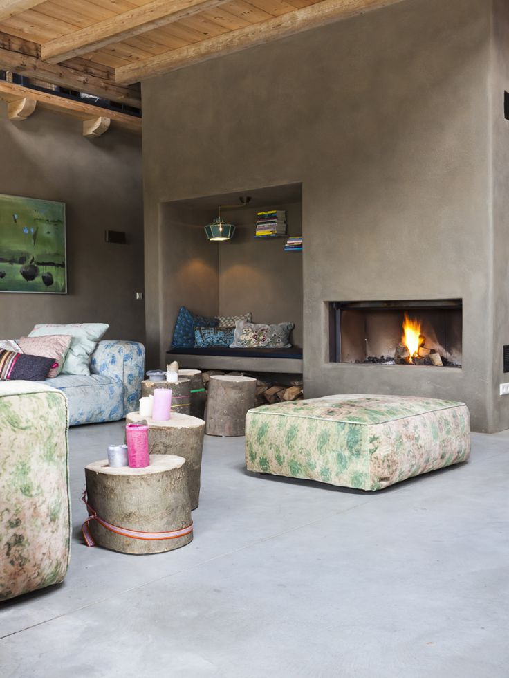 Modern boho living space - built-in fire place, pretty eclectic modular lounge and rustic tree stump side tables.