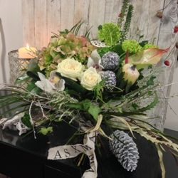 A Christmas hand tied flower bouquet featuring white roses with a seasonal selection of other flowers, foliages and added sparkle.