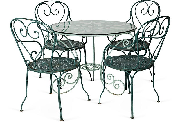French iron garden dining set. pale green round table with a glass top and four chairs.