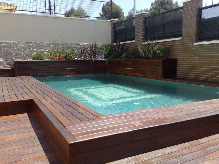 Piscina con tarima de madera IP y jardineras con cascadas integradas.